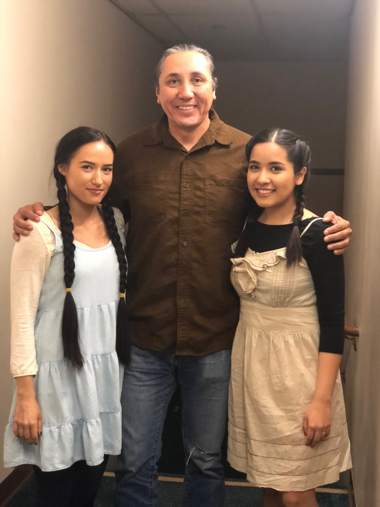Two young sisters smile with an older relative between them.