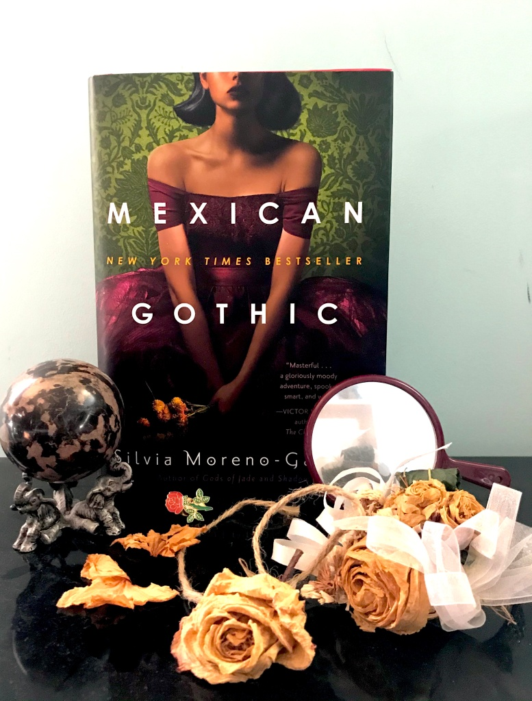 Book cover for Mexican Gothic by Silvia Moreno-Garcia with yellow roses and a globe.