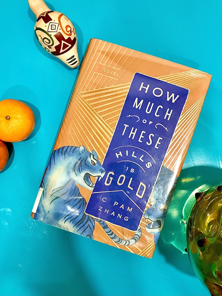 Book cover for How Much of These Hills is Gold with Blue Tigers and oranges beside it.